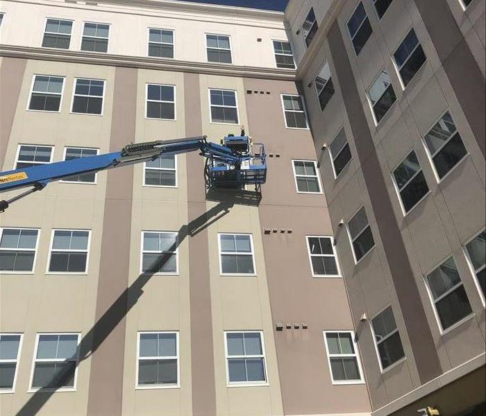 Technician on a lift outside 3 floors up getting ready to clean the dryer vents