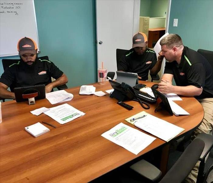 A male crew chief and two male technicians sitting at a conference table going over DryBook Mobile training.