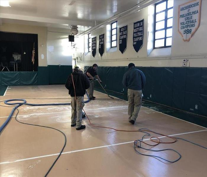 SERVPRO technicians cleaning up flood water from a gym